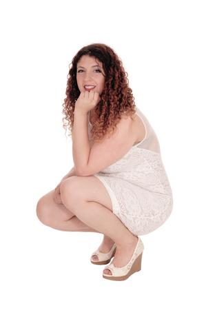 Una hermosa mujer joven con un vestido blanco agazapado en el suelo con una mano debajo de la barbilla, aislado en fondo blanco.