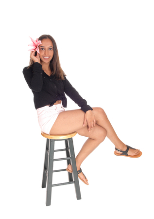A smiling beautiful young woman in shorts, sitting on a green chair holding a pink lily on her hear, isolated for white background.