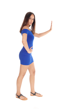 Lovely young woman in a blue short dress holds her hand up to sign stop, isolated for white background.