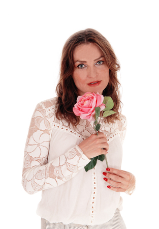 A beautiful young Caucasian woman in a lace blouse and brunette hair holding a pink rose in her hand, isolated for white background.