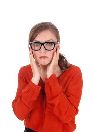 A young afraid looking woman with her hands on her face wearing black glasses standing isolated for white background.