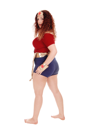 A pretty woman in a costume of a super woman with long curly hair and shorts, bare feet, isolated for white background.