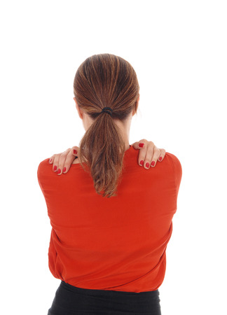 A young woman standing from the back in a closeup and hugging herself with her hands on her shoulder, isolated for white background.