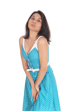 A beautiful woman in a blue dress standing with her hands between her legs, need to pee, isolated for white background.