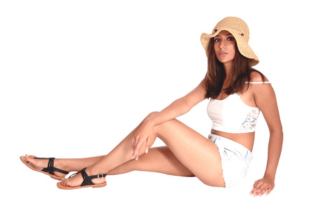 A young beautiful woman siting in shorts on the floor wearing a straw hat and sandals, looking into the camera, isolated for white background Reklamní fotografie