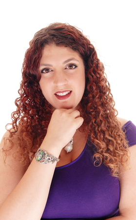 A closeup portrait of a beautiful woman with curly brunette hair whit her hand under her chin, isolated for white background