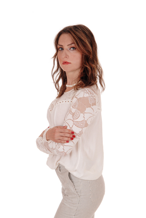 A beautiful young woman in a lace blouse and brunette hair standing in  dress pants in profile, isolated for white background Stock Photo