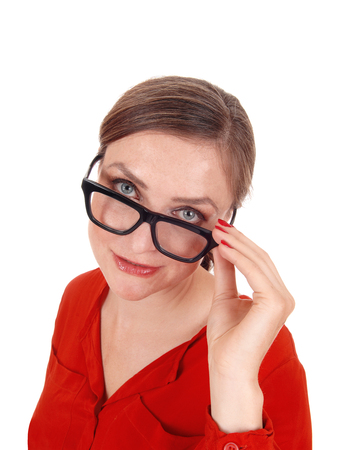 A young afraid looking woman with her hands on her glasses  standing isolated for white background Stock Photo