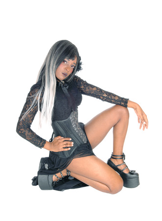 A gorgeous African American woman crouching in a black corset and gray black hair, isolated for white background Stok Fotoğraf