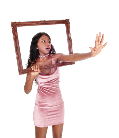 A very upset African woman in a pink dress reaching trough a picture frame, saying stop, no, isolated for white background Stock Photo