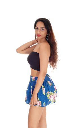 A beautiful East Indian woman standing in a short skirt and black top, with one hand on her head, isolated for white background