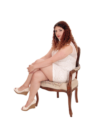 A full figured young woman sitting in a beige lace dress on anarmchair, with curly brunette hair, isolated for white background Stock fotó