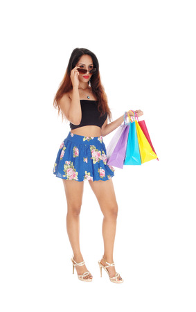 A beautiful young woman standing, holding her sunglasses and  colorful shopping bags, isolated for white background