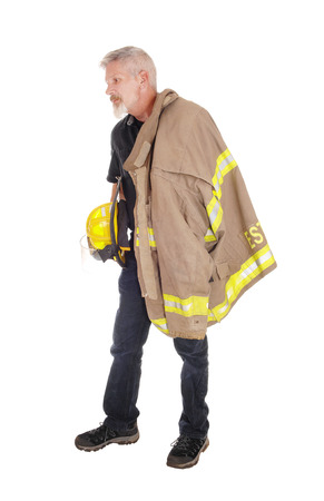 A middle age firefighter man standing in profile with his jacket over his shoulder and helmet in his hand, isolated for white background  Stock Photo