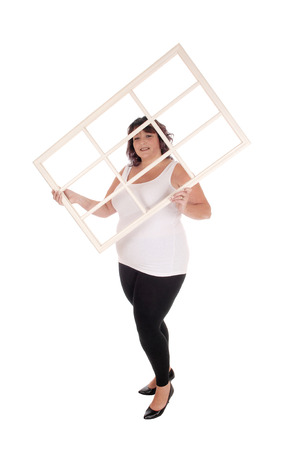 An oversized woman in her forties standing in a white t-shirt and tights  holding up an window frame, isolated for white background
