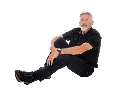 A gray haired middle age man dressed in black and wearing a gray  beard, sitting on the floor and relaxing, isolated for white background