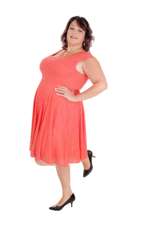 A beautiful woman standing on one leg, in a red dress in profile in  her forties, isolated for white background  Stock Photo
