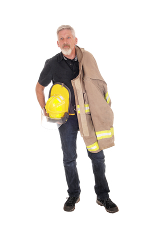 A middle age firefighter man standing from front with his jacket over his shoulder and helmet in his hand, isolated for white background