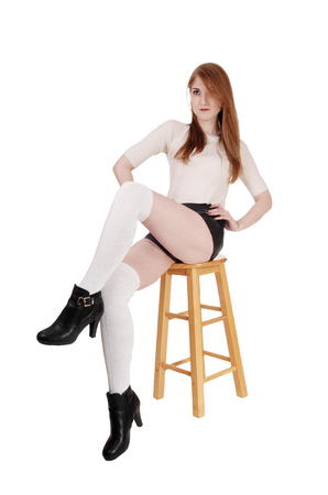 A lovely brunette woman sitting on chair in shorts and long white socksand high heels with legs crossed, isolated for white background