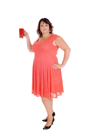 An overweight woman in a red dress standing in profile with a necklace