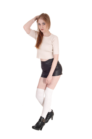A young lovely brunette woman standing over white background in black leather shorts and long white socks an high heels