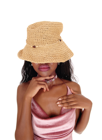 An African woman portrait standing with a straw hat over her eyes and finger under her chin whit big lips, isolated for white background  Stock Photo