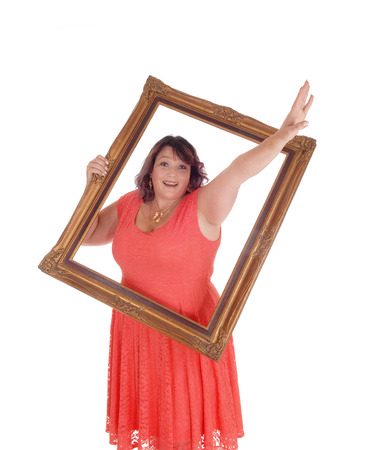An over sized woman in a red dress holding a picture frame and waving with her hand trough, isolated for white background  Stock Photo