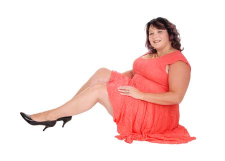 Een mooie grote vrouwenzitting in een rode kleding in de vloer, die in de camera glimlacht, die voor witte achtergrond wordt geïsoleerd