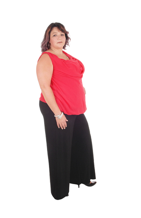 Beautiful full sized woman standing in a red blouse and black trousers in profile, isolated for white background