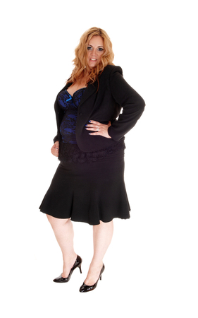 A lovely oversized woman in a black business suit standing in high heels, isolated for white background Stockfoto