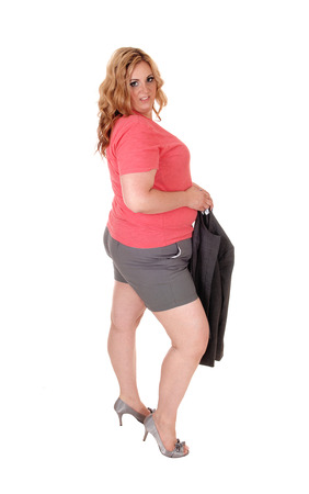 A oversized young woman standing in shorts and pink t-shirt and heels holding her jacket, isolated for white background
