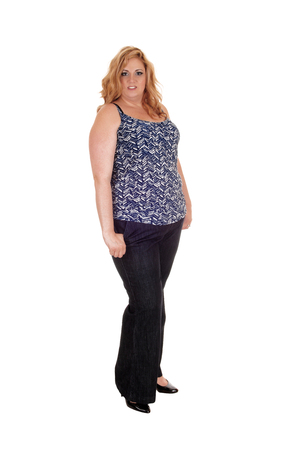 A heavy woman standing in black dress pants and blouse with blond long