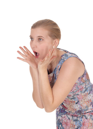 A beautiful woman scared bending forwards with her mouth openand screaming, isolated for white background Stock Photo