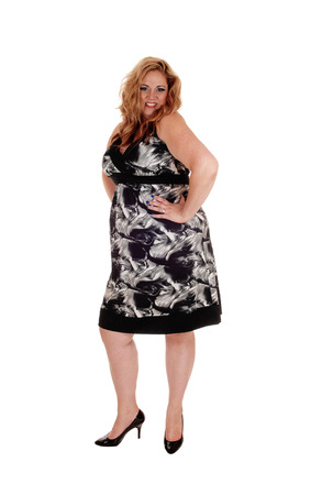 A overweight woman standing in a black gray dress and blond long hair