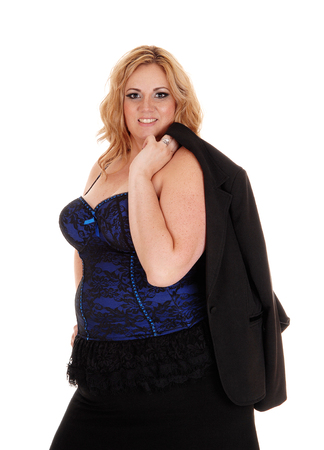 A attractive full sized woman in a blue black corset looking into camera with her jacket over her shoulder, isolated for white background