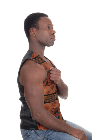 A tall handsome African American man sitting with his fist on his