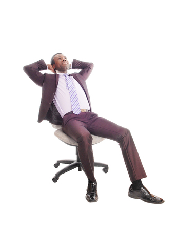 A handsome African American business man sitting on a chair relaxing,  with his hands behind his head, isolated for white background