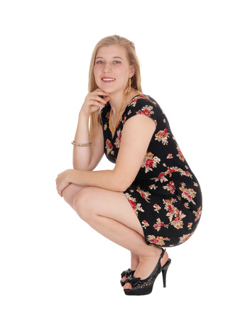 A lovely young blond woman in a black dress with flowers in crouchingon the floor in high heels, isolated for white background Banque d'images - 94296214