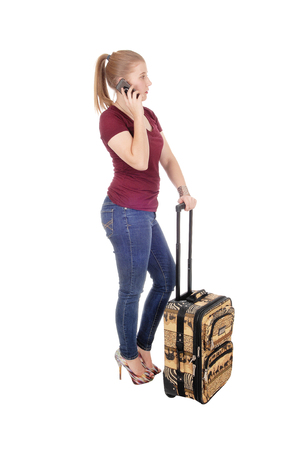 A young blond woman standing in jeans and sweeter with her suitcase and talking on her cell phone, isolated for white background
