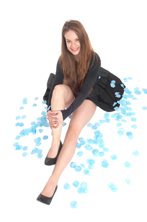 A lovely young woman sitting on the floor surrounded by blue rose