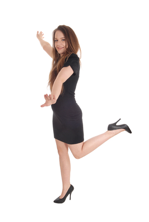A full body image of a young beautiful woman dancing in a black dress with one leg lifted up, isolated for white background