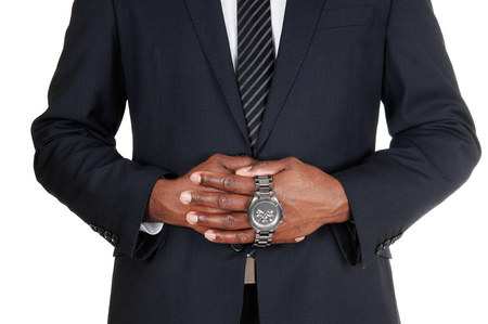The middle section of an African man in a dark suit holding his wristwatch with both hands, isolated for white background