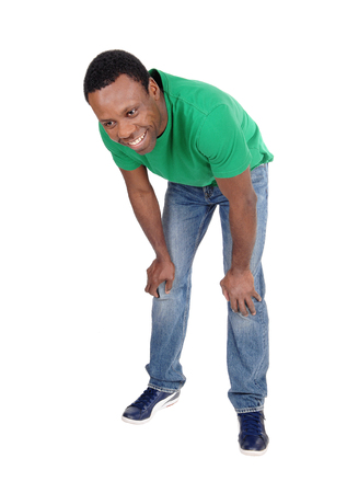 A happy smiling African American man standing in a green polo shirtand jeans bending forwards, isolated for white background