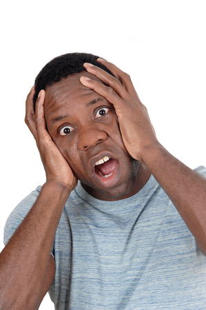 A young African American man looking horrified and scary with hishands on his head and big eyes, isolated for white background Foto de archivo