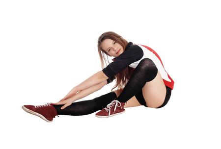 Eine junge dünne Frau, die auf dem Boden im Studio ausdehnt ihren Körper sitzt und erreicht für ihre Füße, lokalisiert für weißen Hintergrund Standard-Bild