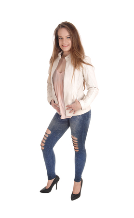 A portrait image of a beautiful young woman in jeans and a white leather jacket standing isolated for white background