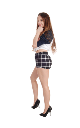 A full length image of a young slim woman standing in checkeredshorts and heels, isolated for white background