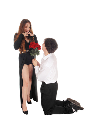 A young man kneeling in front of hid girlfriend with some red roses in