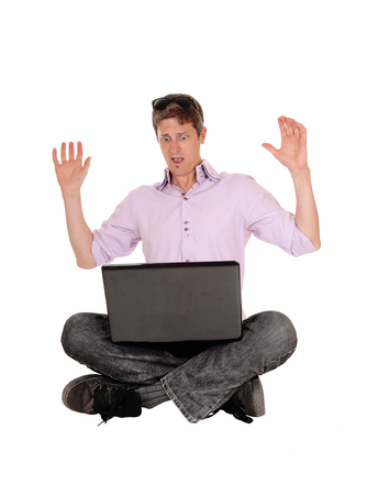 A young man sitting on the floor with his laptop on his knees lifting his hands what he sees on the screen, isolated for white background