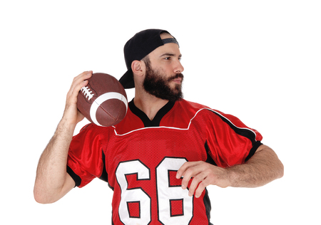 An American football player standing with his ball in his hand in a 